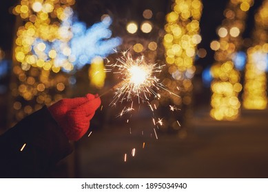 hand with a sparkler on the background of night lights. festive lighting of the city with a sparkler on the background of night lights. festive lighting of the city