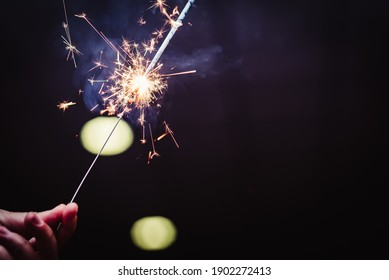 hand with sparkler on black background and party lights