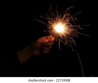 hand with sparkler on a black background
