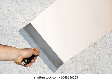 Hand with a spatula aligning the plastered wall