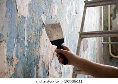 hand with a spatula cleans the wall from Wallpaper