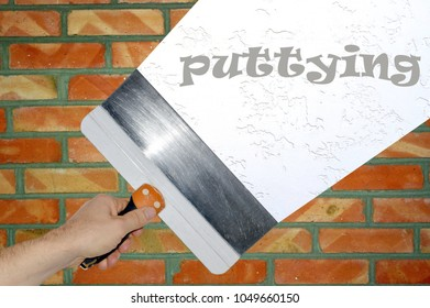 Hand with a spatula, a trowelling brick wall and an inscription of puttying