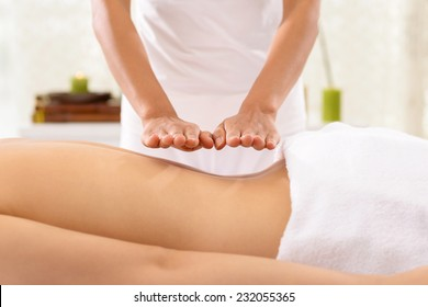 Hand of specialist doing reiki treatment to the woman