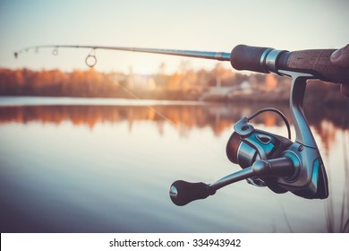 hand with spinning and reel on the summer lake