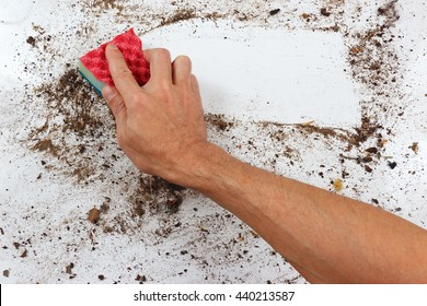 Hand with sponge cleans a dirty surface