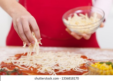 Hand sprinkle grated cheese from a bowl on a half prepared pizza - close up, shallow depth