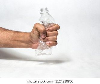 hand squashing empty plastic water bottle resembling ban of single use plastic recycle