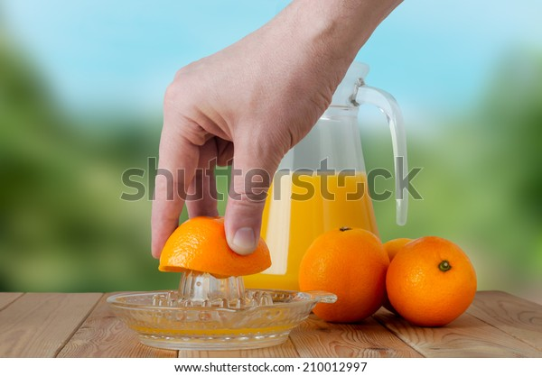 A hand squeezing juice from an orange on a manual glass squeezer.  Set on a wooden planked table with a group of three oranges and a glass jug of juice.  Outdoor background of soft foliage.