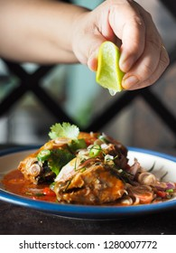 hand squeezing lime over thai mackerel in tomato sauce with herbs and chili as spicy salad.