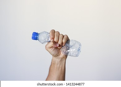 Hand squeezing Plastic Bottle representing movement against pollution and for recycling.