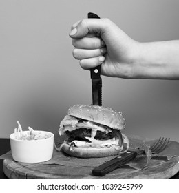 Hand stabbing with knife burger lying with portion of salad and fork on round wooden plate covered with piece of kraft paper against orange wall on background. Delicious fast food meal, grilled dish.