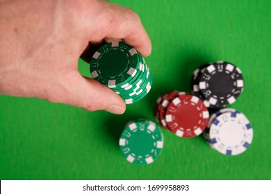 Hand with stack of poker chips isolated on green background