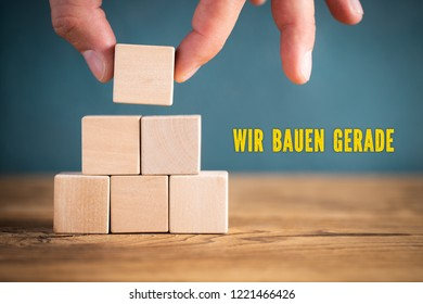 """hand is stacking blank cubes and the message """"under construction"""" in German"""