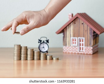 hand stacking coin and wooden house on desk, Property investment and house mortgage financial concept