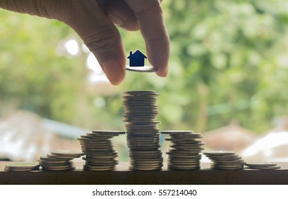 hand stacking of coins with house model,concept idea for save money and business.