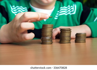 Hand stacking counting coins (money) on wooden table