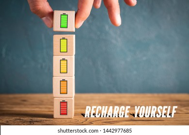 "Hand stacking cubes with icons symbolizing recharging mental engergy and the message ""recharge yourself"""