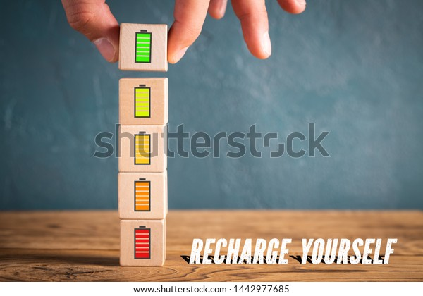 """Hand stacking cubes with icons symbolizing recharging mental engergy and the message """"recharge yourself"""""""