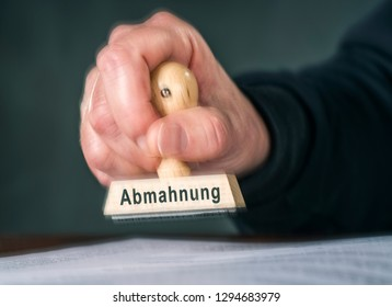 "Hand with a stamp with the word ""Abmahnung"" for dissuasion"