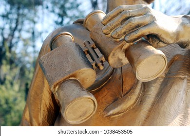 The hand of the statue with its telescope.