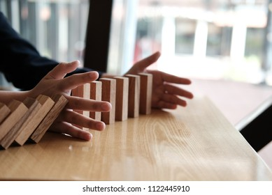 hand stopping effect of domino continuous toppled. busineeman protecting falling wood block. solution & strategy in business. problem solving concept
