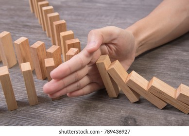 hand stopping wooden block domino. concept prevent and solution.