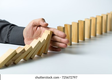 Hand stopping wooden blocks from falling in the line of domino