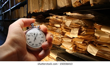 Hand with stopwatch, paper documents stacked in archive