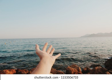 Hand stretched out in front of the sea