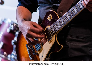 A hand strums at electric guitar strings in front of the blurred background of a drum kit as a lead guitarist plays a chord
