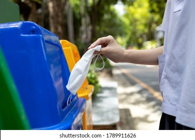 Hand of student girl is throwing away the used protective face mask in the garbage bin,trash bins that separates only a mask and infectious waste in school,prevent the spread of COVID-19,Coronavirus