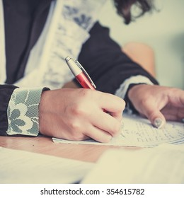 Hand of a student in a school uniform writes in a notebook.