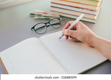 Hand of student studying and writing in notebook