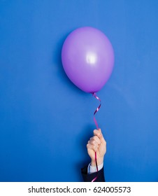 Hand in a suit holding flying up balloon.