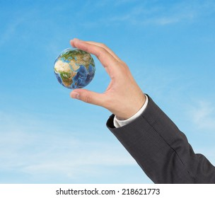 A hand in a suit holding globe, Africa and Asia view. Elements of this image furnished by NASA