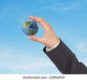 A hand in a suit holding globe, America view. Elements of this image furnished by NASA
