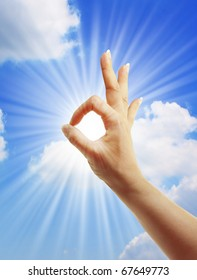 hand sun and blue sky with  showing freedom or solar power concept