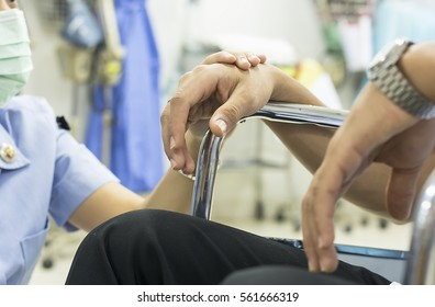 A hand support men in the wheelchair in the hospital.