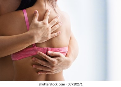 Hand supporting breast cancer victim, on the back of woman using bra with one strap only