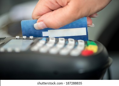 Hand swiping debit card on pos terminal
