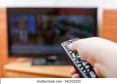 Hand switches TV channels with news by remote control in living room