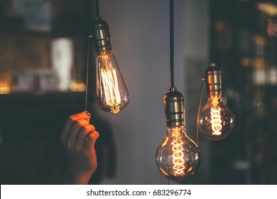 Hand switching off the light bulbs, vintage light bulbs at coffee shop