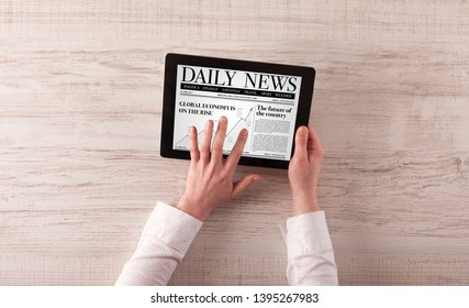 Hand with tablet reading news on tablet