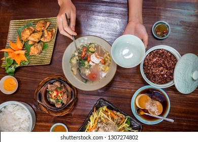 Hand take a spoon of soup on wood table. Standard Vietnamese meals include brown rice, fried chicken, tiger prawn sour soup, braised cow's tendon, mango salad, dessert of flan.