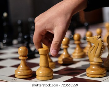 Hand takes chess pawn