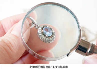 hand takes earring with big blue topaz and white diamonds around, jeweler looking at jewelry through magnifying glass, jewerly inspect and verify, pawnshop concept