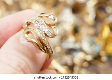 hand takes golden ring, jewerly inspect and verify, pawnshop concept, jewerly shop concept