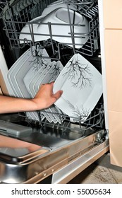 hand takes a plate from the open dishwasher