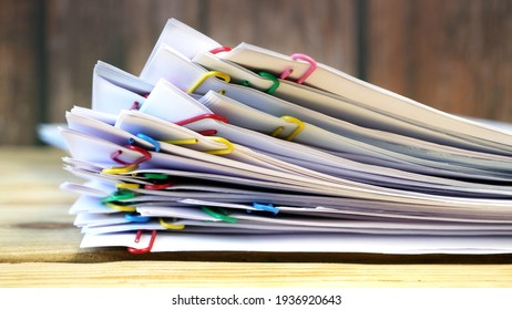 Hand takes stack of documents with binder clips wooden table