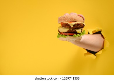 Hand taking a big burger through torn yellow paper background with copy space. Can't resist a tasty fast food dish.